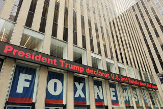 A news ticker displays headlines from the meeting of U.S. President Donald Trump and Russia's President Vladimir Putin in Helsinki, Finland on the News Corp building in New York