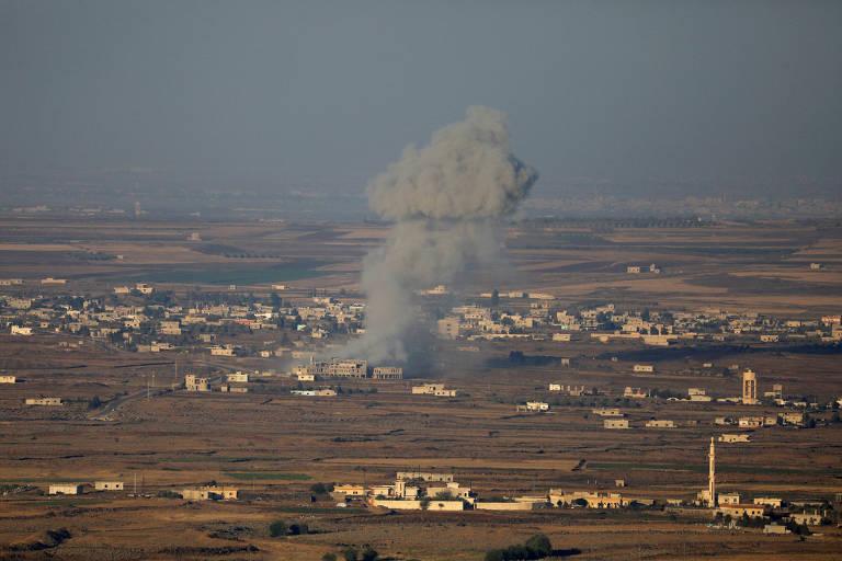 Cogumelo de fumaça cinza sobe sobre cidade síria, vista do alto