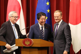 Japanese Prime Minister Shinzo Abe, European Commission President Jean-Claude Juncker and European Council President Donald Tusk smile after their joint press conference of Japan-EU summit at Abe's official residence in Tokyo