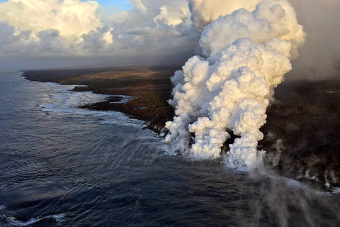 TOPSHOT - This handout photograph obtained July 16, 2018, courtesy of the US Geological Survey (USGS), shows laze plumes rising where lava pours into the sea on the south margin of the fissure 8 flow of the K?lauea volcano, July 15, 2018 in Hawaii. 