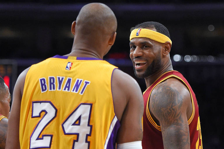 Então jogador do Cleveland Cavaliers, LeBron James sorri para o ex-jogador do Los Angeles Lakers  Kobe Bryant durante parida na NBA