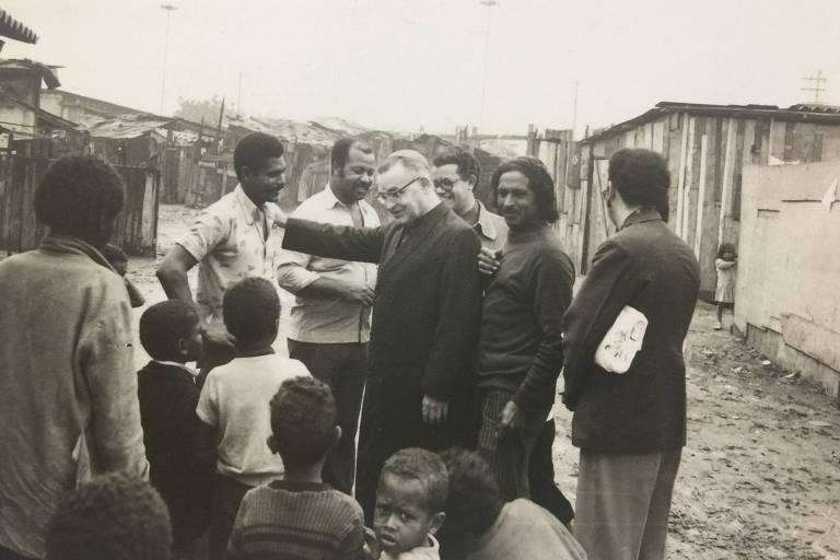Dom Paulo cercado de pessoas em meio a uma comunidade