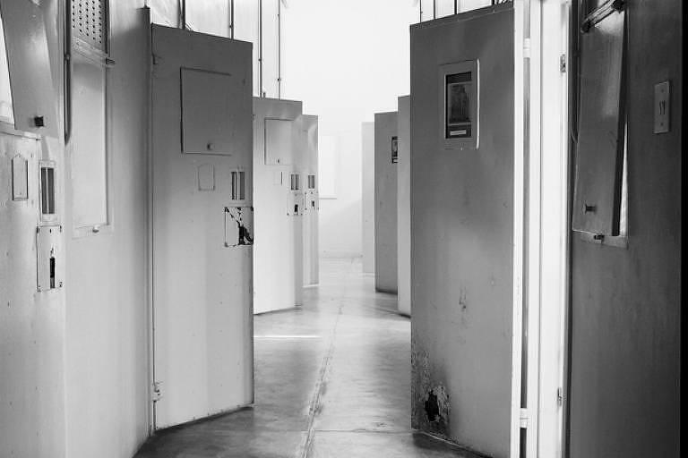 Portas de prisão brancas são vistas entreabertas em preto e branco.