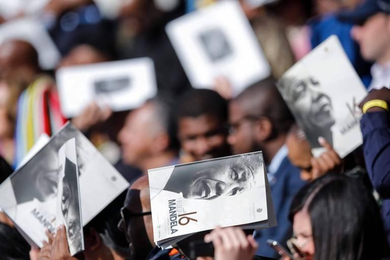 Cinco livretos brancos com uma foto de Mandela em preto-e-branco aparecem cobrindo a cabeça de algumas pessoas na plateia.