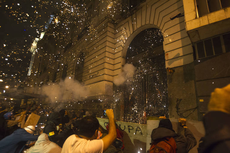 RIO DE JANEIRO, 07/10/2013: Em um dos atos mais violentos dos protestos de hoje a noite, manifestantes tacam pedras, paus e ateiam fogo à uma das entradas da Câmara de Vereadores do Rio. Atrás da grade, PMs protegiam a entrada com uma barreira de escudos.