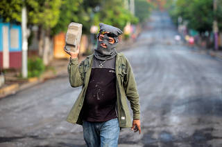 A pro-government supporter carries a paving stone after clashes with demonstrators in the indigenous community of Monimbo in Masaya