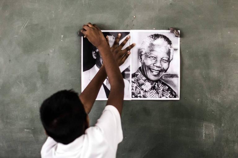 Criança cola pôster em quadro de escola