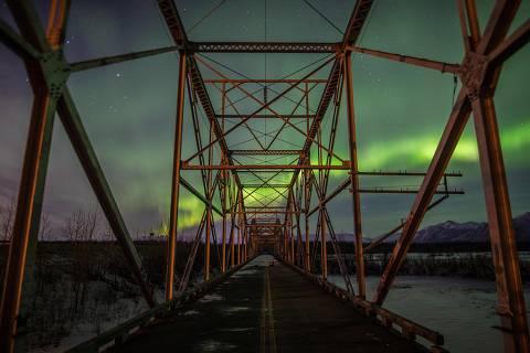 Ponte no Alasca, Estados Unidos, com aurora boreal ao fundo