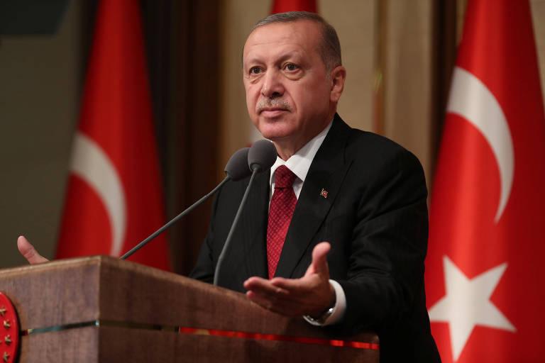 Com terno preto, camisa branca e gravata vermelha, Erdogan se apoia em um púlpito de madeira escura com dois microfones. Ele aparece abrindo as duas mãos apoiando-as no púlpito. Ao fundo, duas bandeiras da Turquia.