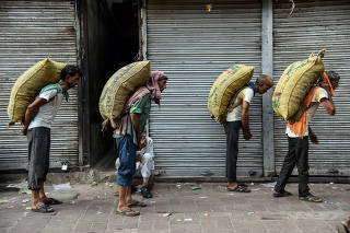 Workers carry sacks of spices on a hot summer morning in the old quarters of Delhi.
