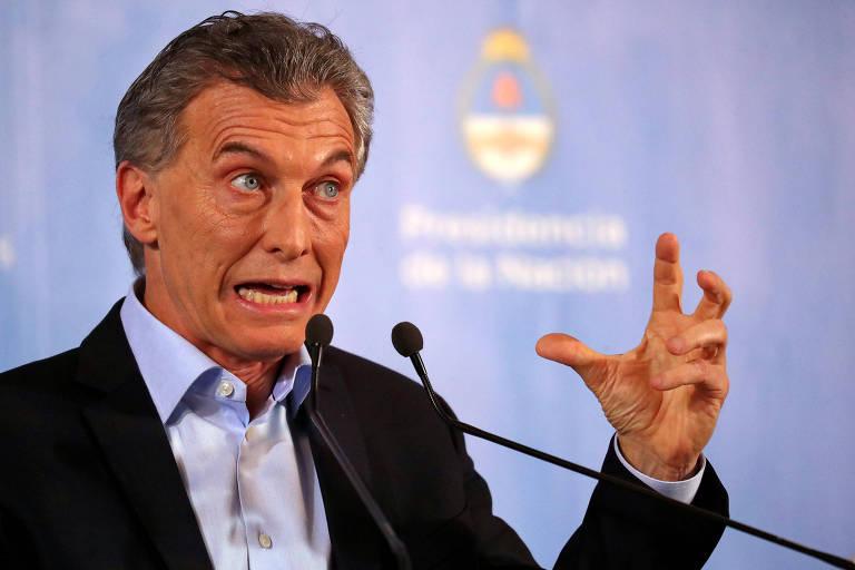 Mauricio Macri, de terno sem gravata, arregala os olhos, abre a boca e gesticula com as mãos diante de um microfone