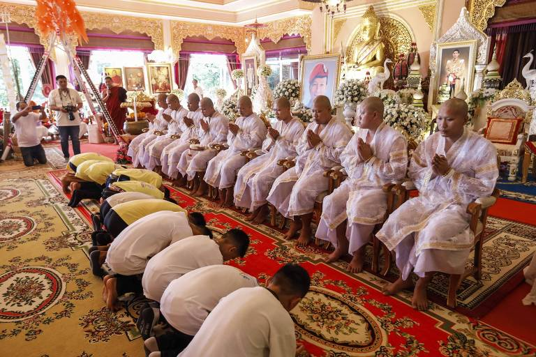 O grupo de garotos que ficou preso em uma caverna na Tailândia (ajoelhados) durante cerimônia em um templo budista