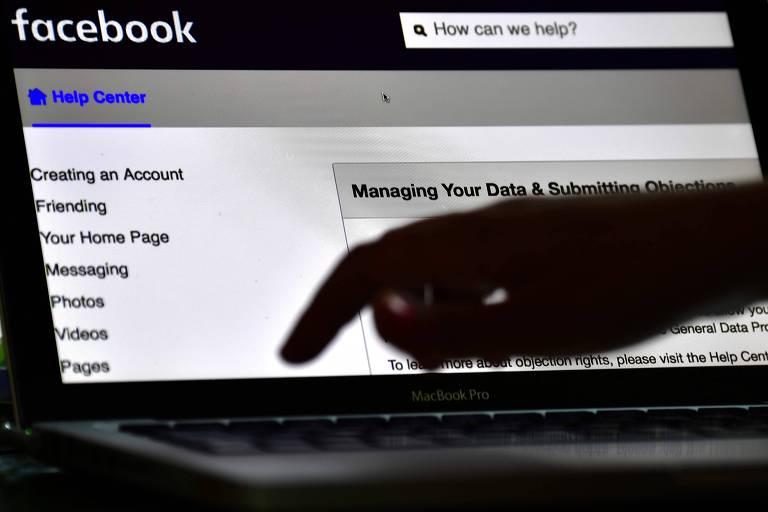 Mulher gerencia sua conta no Facebook; empresa anunciou que vai retirar notícias falsas que causem violência