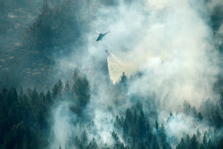 Helicóptero joga água para tentar conter incêndio próximo da cidade de Ljusdal, na Suécia