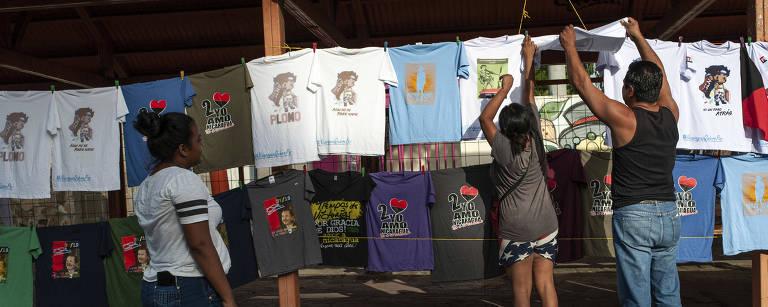 Simpatizantes do governo Ortega observam camisetas estampadas com o rosto do presidente da Nicarágua e com o símbolo do partido da situação, a Frente Sandinista de Libertação Nacional, em Manágua, no 39º aniversário da queda da ditadura Somoza