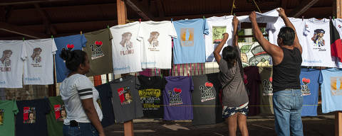 Pro-government supporters check out T-shirts promoting Nicaraguan President Daniel Ortega and The Sandinista National Liberation Front ruling political party, ahead of a rally commemorating the uprising that ousted the Anastasio Somoza family, in Managua, Nicaragua, Thursday, July 19, 2018. Nicaragua marked the 39th anniversary of the 1979 revolution against the dictator Somoza on Thursday amid protest and bloodshed. (AP Photo/Cristobal Venegas) ORG XMIT: XCV103