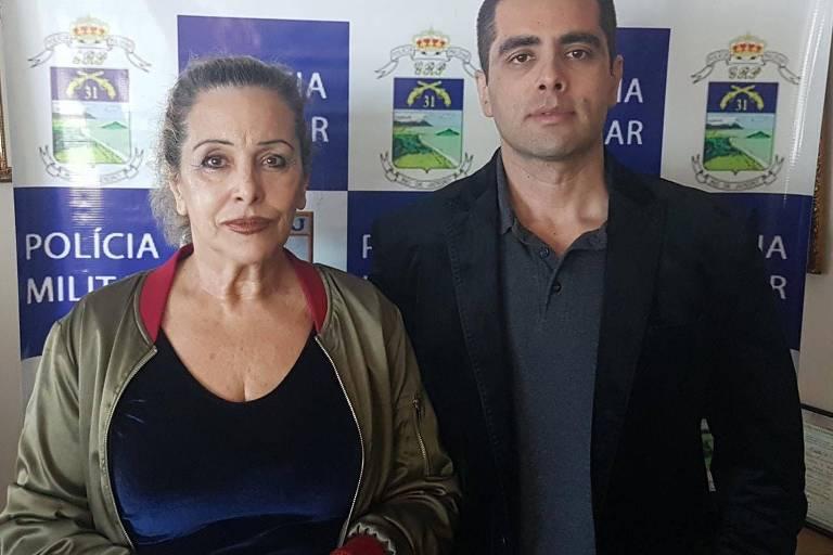 Doutor Bumbum e sua mãe, lado a lado, em foto com nome da PM atrás