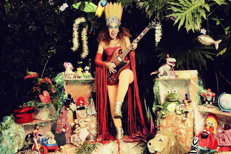 Iara Rennó com um vestido vermelho tocando violão rodeada de animais de mentira em uma floresta