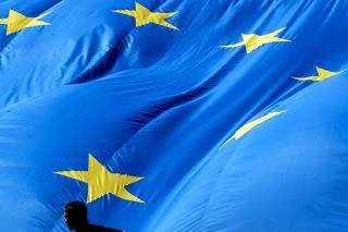 WORKER STANDS IN FRONT OF A 150M EUROPEAN UNION FLAG IN BRUSSELS