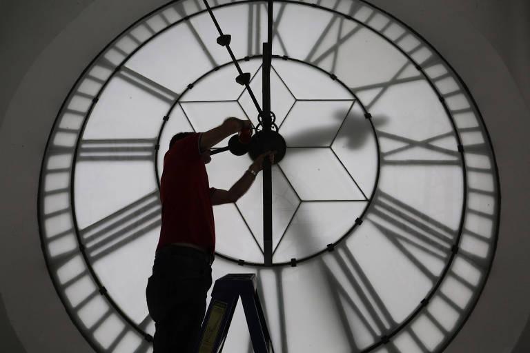 Relojoeiro ajusta relógio da estação da Luz, centro de São Paulo, no fim do horário de verão, em fevereiro de 2018