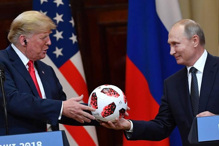 O presidente dos EUA, Donald Trump (à esq.), recebe bola de futebol do colega russo, Vladimir Putin, em entrevista coletiva em Helsinque (Finlândia)