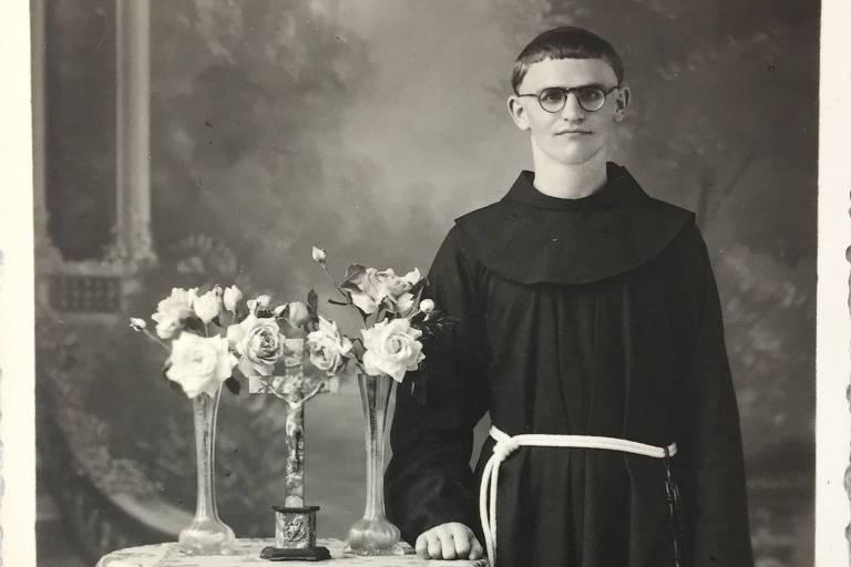 Dom Paulo Evaristo Arns jovem ao lado de mesa com flores