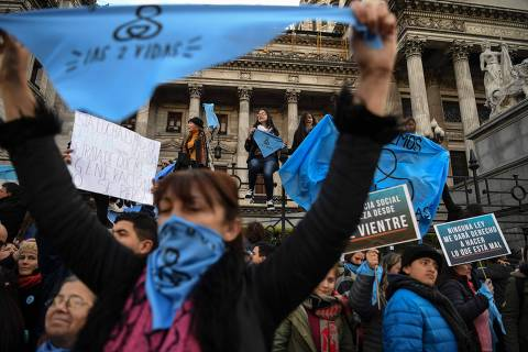 """Demonstrators with blue headscarves against the legalization of abortion, gather outside the Congress building in Buenos Aires, on July 03, 2018. Born as an identity symbol of feminist fights for the right to a legal abortion, the green headscarf brought a new color to the streets in Argentina, where the bill will be debated next August 8. On the other hand, those who oppose the law, recognise themselves with a sky blue headscarf in favor """"of both lives"""". / AFP PHOTO / EITAN ABRAMOVICH ORG XMIT: EAS5005"""