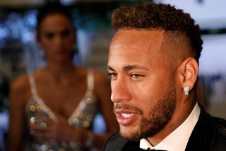 Soccer player Neymar talks to the media as his girlfriend Bruna Marquezine looks at him after posing on the red carpet during an auction to raise funds for his Institute Project Neymar Jr in Sao Paulo