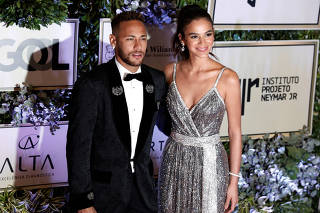 Soccer player Neymar and his girlfriend Bruna Marquezine pose on the red carpet during an auction to raise funds for his Institute Project Neymar Jr in Sao Paulo