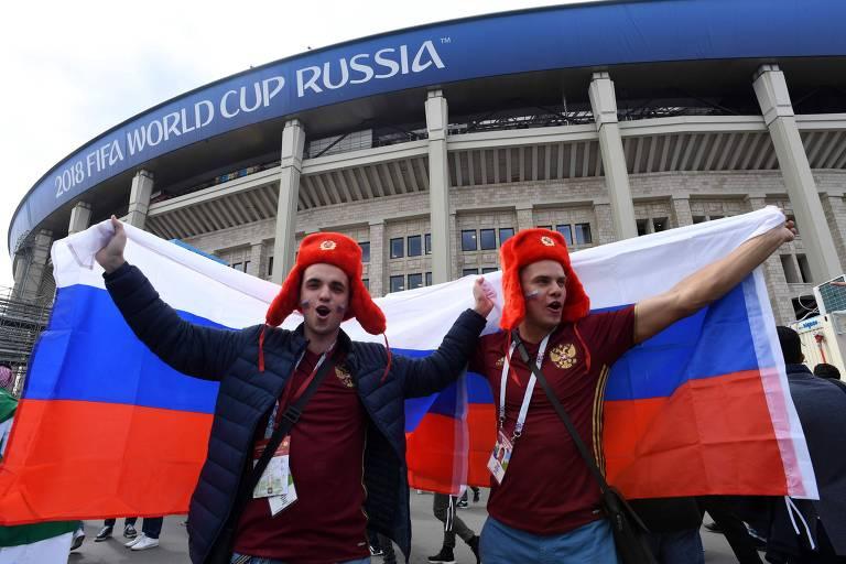 Torcedores russos festejam com bandeiras do país em frente ao Estádio Lujniki, de Moscou
