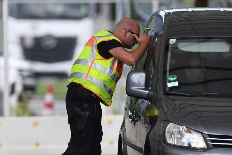 Policial alemão fiscaliza carro na fronteira do país com a Áustria