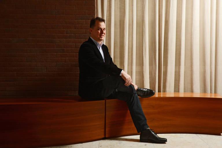 Homem de terno sentado, de pernas cruzadas, num banco de madeira com cortina branca ao fundo