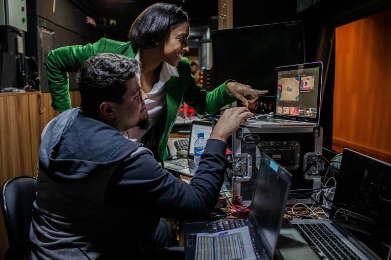 Homem de azul, sentado, e mulher de verde, de pé, olham para tela de computador