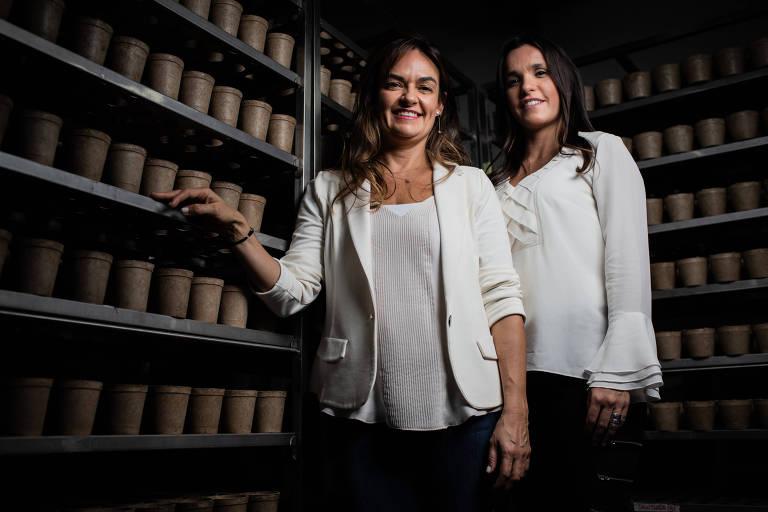 Duas mulheres de camisa branca em frente a prateleiras cheias de vasos