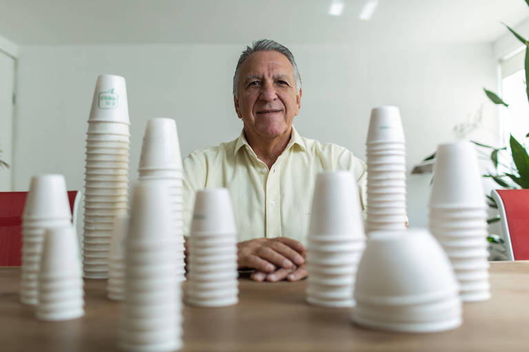 Homem de camisa e cabelos brancos sentado atrás de uma mesa cheia de copos brancos
