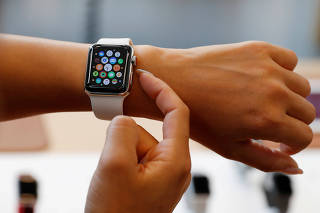 FILE PHOTO: A woman tries a new Apple Watch Series 3 Cellular model after it goes on sale at the Apple Store in Tokyo's Omotesando shopping district
