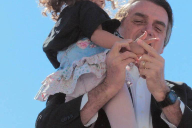 O pré-candidato Jair Bolsonaro (PSL-RJ) ensina criança a fazer o gesto de uma arma