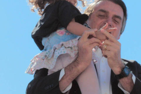 Imagem de Bolsonaro ensinando menina a imitar arma é criticada por presidenciáveis