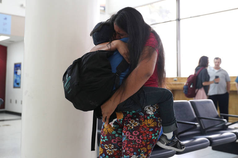 Mulher abraça um menino que leva no colo. Os dois são retratados de perfil, à distância e seus rostos não aparecem. Ao fundo do lado direito, há uma sequência de cadeiras típicas de aeroporto.