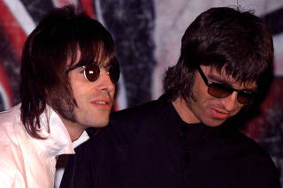 FILE PHOTO: Liam and Noel (R) Gallagher, of the British rock band Oasis, wait for the start of a news conference at a pub in London
