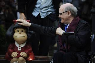 Cartoonist Quino touches a sculpture of his comic character Mafalda, during an opening ceremony of a park of San Francisco in Oviedo