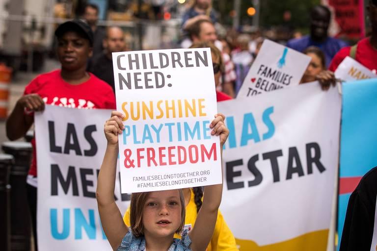 Criança segura cartaz em manifestação que diz, em inglês: crianças precisam de luz do sol, brincadeiras e liberdade