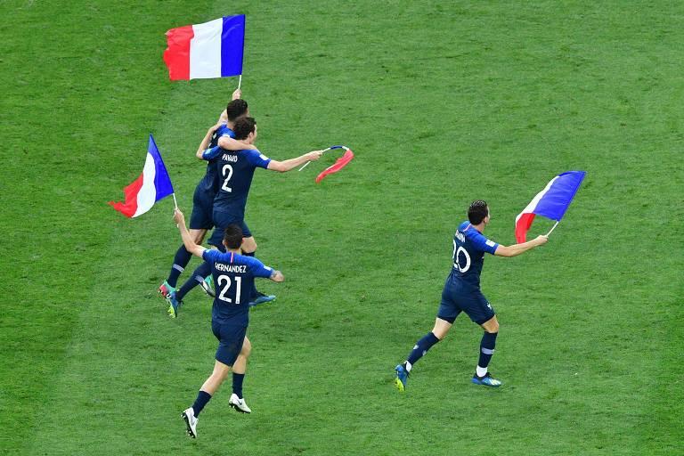 Quatro homens vestidos de azul andam em gramado com bandeiras da França