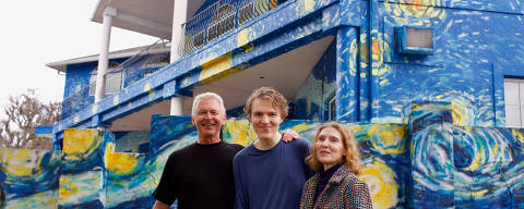 Lubomir Jastrzebski (L) and Nancy Nembhauser (R) pose with their adult son in front of the house with the
