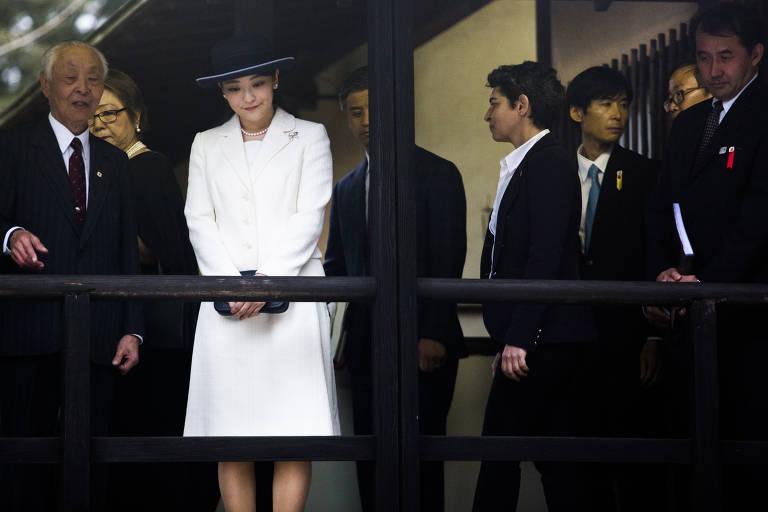 Mako está com vestido branco e chapéu preto, ao lado de um grupo de homens de terno.