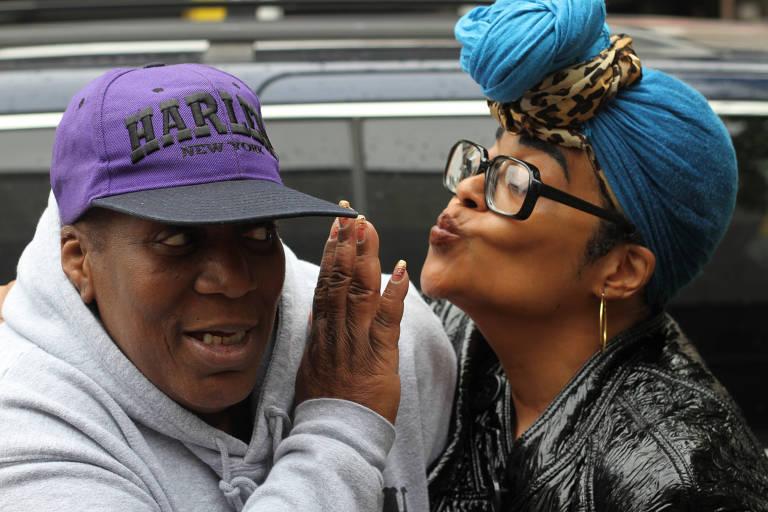 Duas mulheres posam para a foto. À esquerda está uma vestida com um moletom e um boné roxo de aba preta com a palavra Harlem, que levanta a mão para a outra, que usa um turbante azul amarrado para frente e dá um beijo.