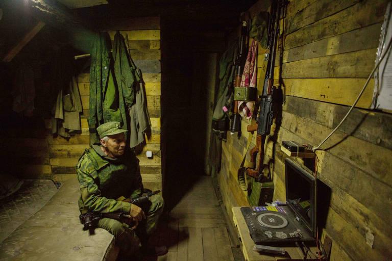 Soldado com uniforme de camuflagem verde está sentado em um barracão de madeira em um banco à esquerda. Em frente a ele há um reprodutor de DVD portátil com tela, um fuzil e outras armas penduradas. Ao fundo à esquerda há uniformes camuflados pendurados.