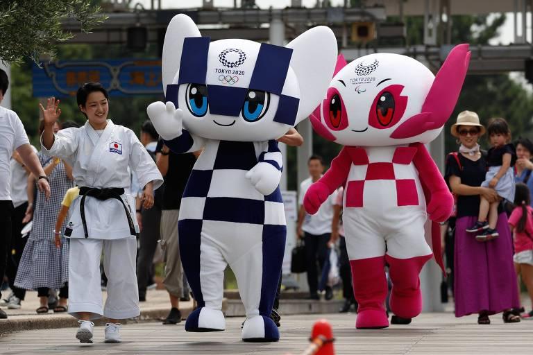 Boneco quadriculado de azul e branco e boneca quadriculada de rosa e branco caminham em rua