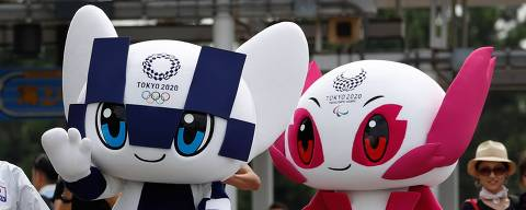 Tokyo 2020 Olympic Games mascot Miraitowa (C) and Paralympic mascot Someity wave with Japanese karateka Kiyo Shimkizu (L) upon their arrival after a parade at Odaiba Marine Park in Tokyo on July 22, 2018.