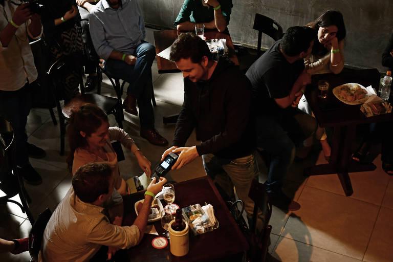 Candidato Humberto Laudares coleta doação eleitoral com maquininha de cartão num bar